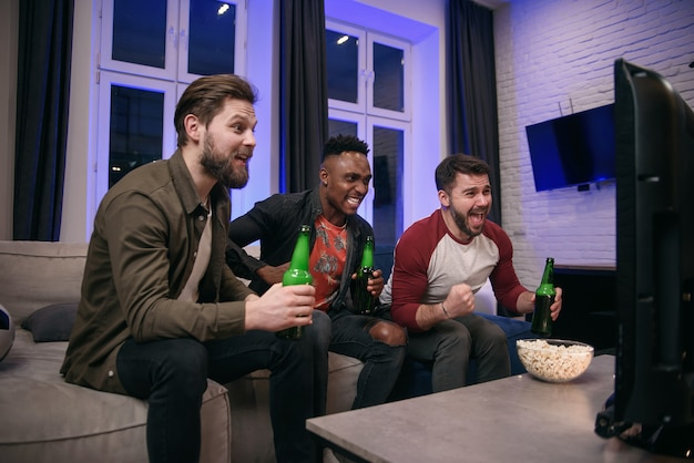 Jeunes joyeux multiraciaux sympathiques applaudissant leur équipe de football préférée avec des cris et des mains pendant le match de sport à la télévision