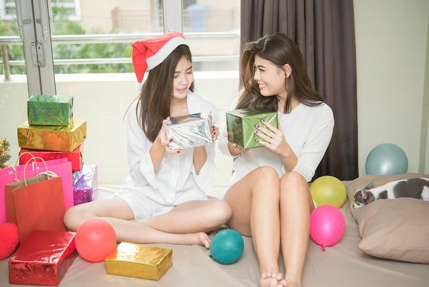 Jeunes lesbiennes célébrées avec des ballons et des coffrets cadeaux dans la chambre. heureux amis relati