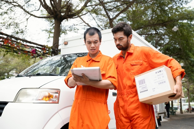 Les jeunes livreurs vérifiant les informations pour la livraison près de la voiture