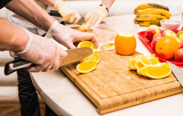 Jeunes mains propres de chef coupant l'orange sur la table