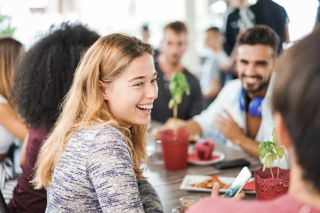 Jeunes mangeant le petit déjeuner et buvant des smoothies au bar-restaurant - focus sur le visage de la fille