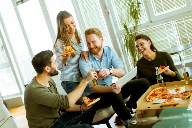 Jeunes mangeant une pizza, buvant du cidre et regardant une tablette numérique dans la chambre