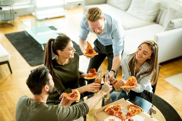 Jeunes mangeant des pizzas et buvant du cidre dans la chambre