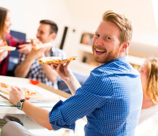 Jeunes mangeant des pizzas dans la chambre