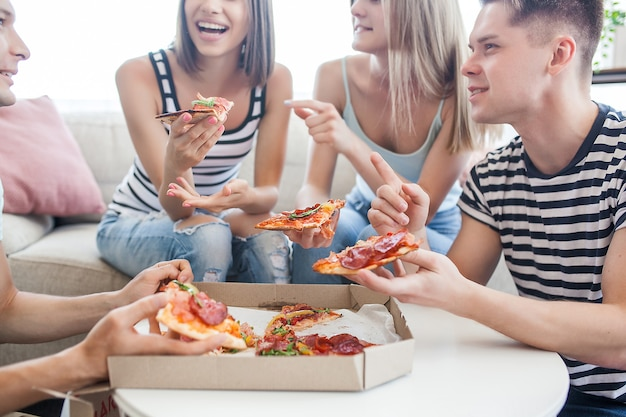 Les jeunes mangent de la pizza. groupe d'amis en train de déjeuner à l'intérieur. des amis drôles ensemble.