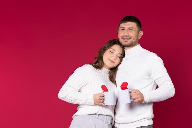 Jeunes mariés amoureux de tasses de thé blanc sur fond rouge avec espace latéral.