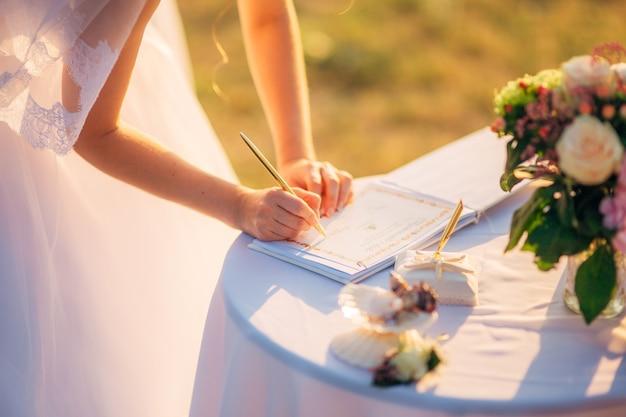 Les jeunes mariés apposent leur signature sur l'acte d'enregistrement d'un mariage