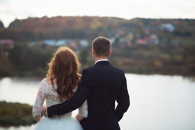 Jeunes mariés au jour du mariage en marchant à l'extérieur dans la nature du printemps.