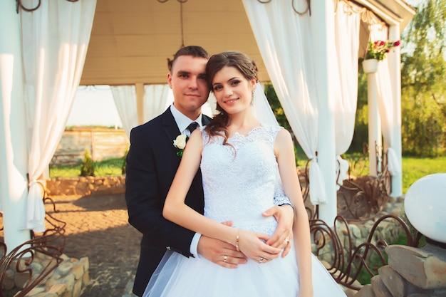 Jeunes mariés au jour du mariage en marchant à l'extérieur sur la nature du printemps. couple nuptial, heureux jeune femme et homme embrassant dans un parc verdoyant. couple de mariage aimant en plein air. jeunes mariés