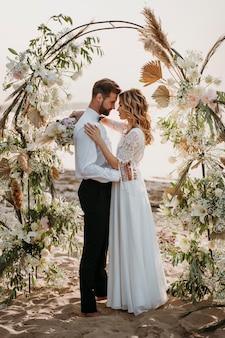 Jeunes mariés ayant leur mariage à la plage