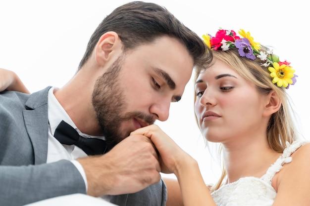 Jeunes mariés de baiser caucasien et câlin sur fond blanc.