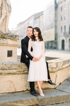 Jeunes mariés chinois mignon jeunes mariés viennent de se marier en couple posant sur les escaliers en pierre dans les rues de la vieille ville le jour du mariage.