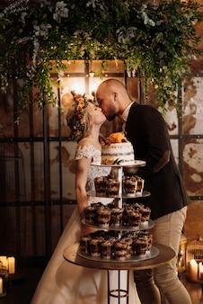 Les jeunes mariés coupent et goûtent joyeusement le gâteau de mariage