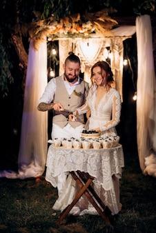 Les jeunes mariés coupent, rient et goûtent joyeusement le gâteau de mariage