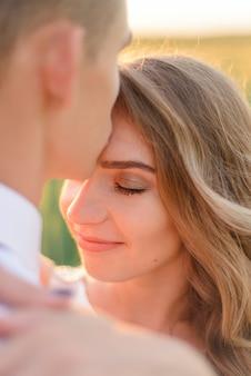 Jeunes mariés dans un champ de blé. un homme embrasse un bien-aimé sur le front.
