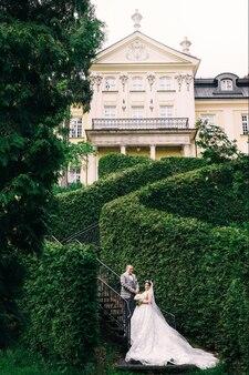 Les jeunes mariés dans les escaliers sur un fond de buissons et de bâtiment. mariée en robe de mariée avec robe longue queue.