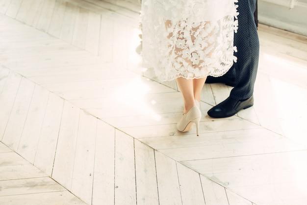 Jeunes mariés dans un studio lumineux, photo sans visages. parquet de sol