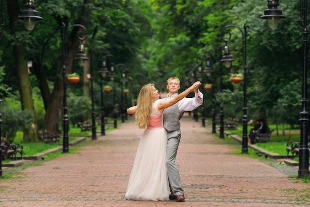 Les jeunes mariés dansent dans le parc
