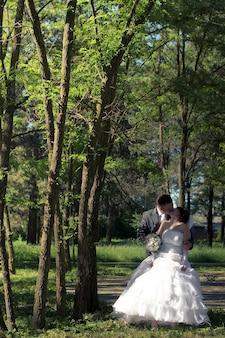 Jeunes mariés debout ensemble sous l'arbre