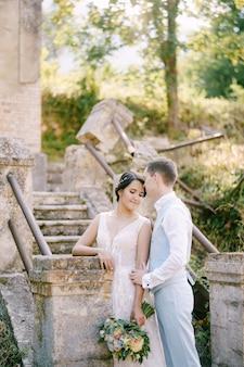 Jeunes mariés debout près des escaliers de l'ancien clocher près de l'église de prcanj le