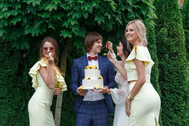 Les jeunes mariés et les demoiselles d'honneur s'amusent et mangent ensemble un gâteau de mariage à l'air frais lors d'un banquet de mariage.