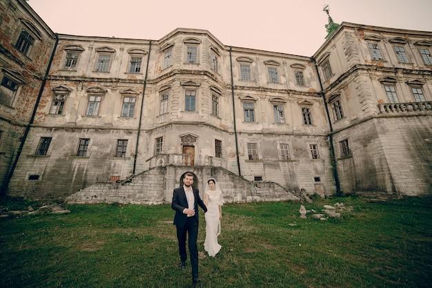 Jeunes mariés devant une grande maison