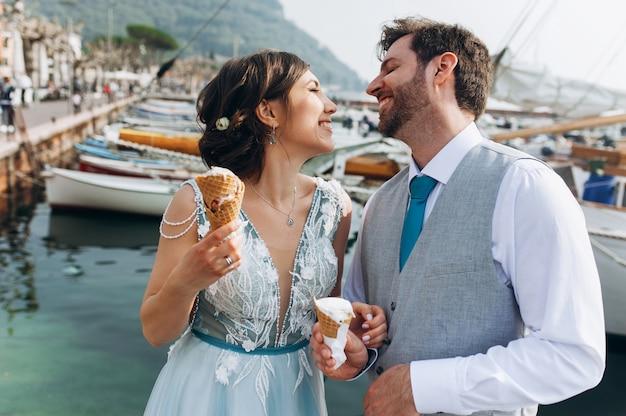 Les jeunes mariés drôles mangent de la crème glacée debout devant les bateaux