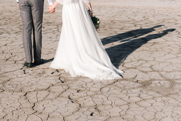 Jeunes mariés sur un fond de terre fissurée