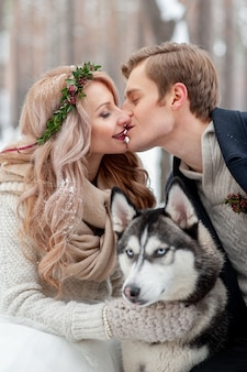 Les jeunes mariés gais s'embrassent sur fond de husky. mariage d'hiver. espace copie
