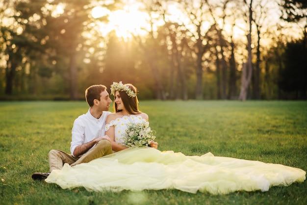 Jeunes mariés heureux assis sur l'herbe dans le parc au coucher du soleil