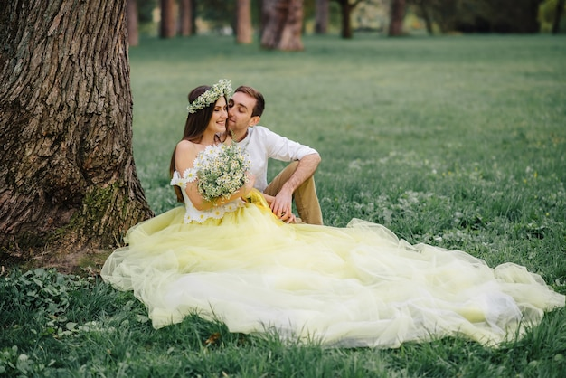 Jeunes mariés heureux assis sur l'herbe près de l'arbre dans le parc