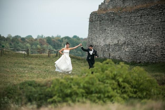 Jeunes mariés heureux danser sur l'herbe