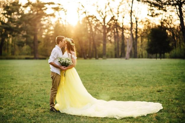 Jeunes mariés heureux étreignant dans un parc de printemps au coucher du soleil