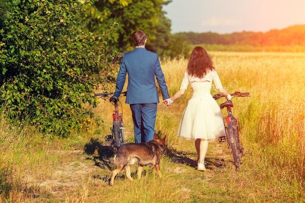 Les jeunes mariés heureux portent des vélos dans le champ de blé à la caméra