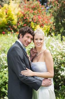 Jeunes mariés heureux romantiques embrassant regarder la caméra