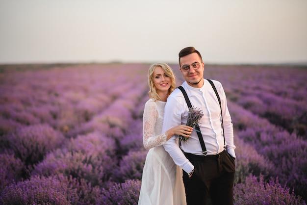 Les jeunes mariés heureux se tiennent dans un champ de lavande en fleurs au coucher du soleil