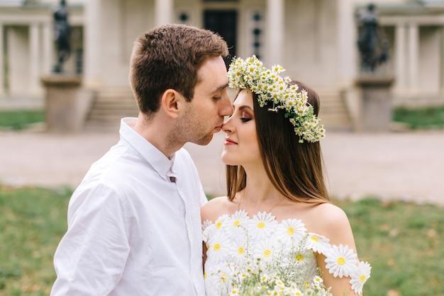 Jeunes mariés heureux serrant dans un parc au printemps, gros plan