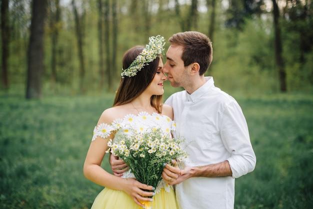Jeunes mariés heureux serrant dans un parc au printemps