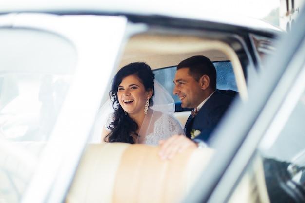 Jeunes mariés à l'intérieur d'une voiture classique. ils sont heureux.