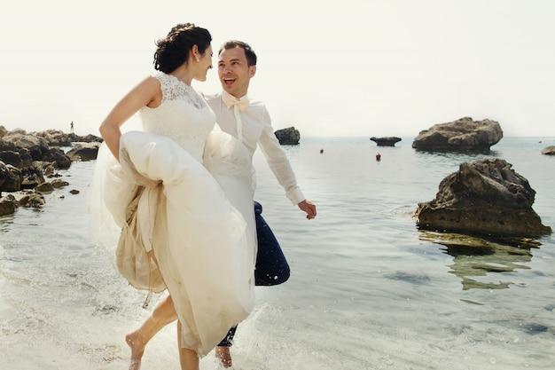 Des jeunes mariés joyeux courent le long de la plage