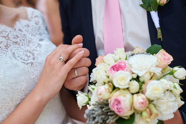 Jeunes mariés, main dans la main avec bouquet de mariée
