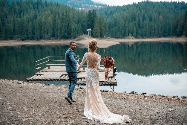 Jeunes mariés, main dans la main lors de la cérémonie de mariage sur le magnifique lac