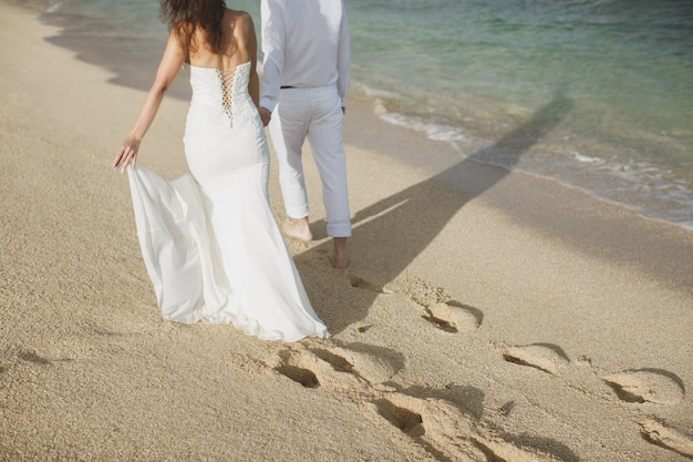 Jeunes mariés marchant dans le sable
