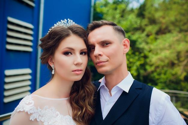 Jeunes mariés marchant dans la ville, jour du mariage, concept de mariage. jeunes mariés en milieu urbain. jeune couple va dans un escalier au jour du mariage.
