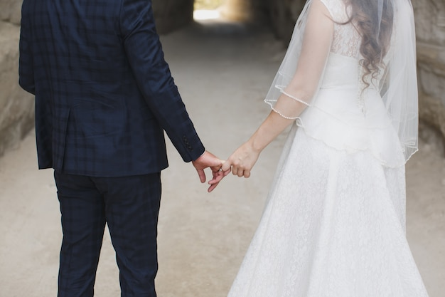 Jeunes mariés marchant ensemble en tenant leurs mains