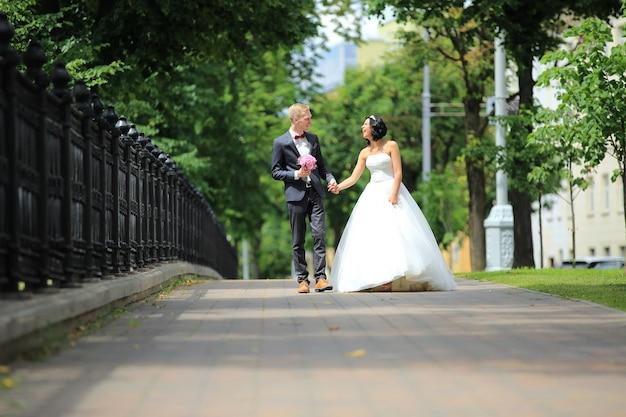 Jeunes mariés marchant à l'extérieur dans des vêtements de mariage après la cérémonie