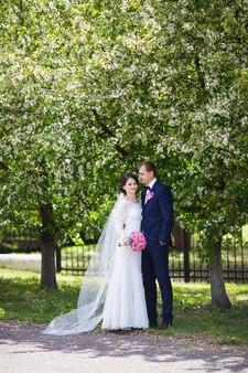 Les jeunes mariés et mariée avec bouquet de mariage rose dans le jardin fleuri