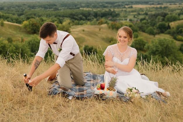 Les jeunes mariés ont fait un pique-nique dans la nature. la mariée et le marié aimant boivent du champagne assis sur un couvre-lit et se regardent après la cérémonie de mariage.