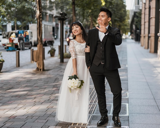 Jeunes mariés posant ensemble dans la rue