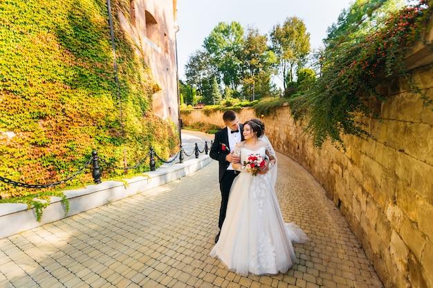 Jeunes mariés près du bâtiment et mur recouvert de lierre. la mariée tient un bouquet et le marié la serre dans ses bras